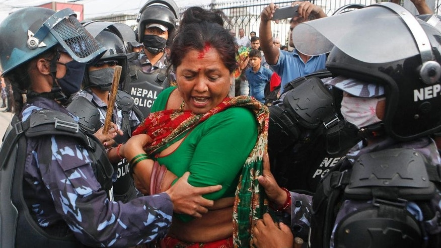 Nepalese policewomen try to stop a Hindu activist as they block a road and try to enter a restricted area near the Nepalese Constituent Assembly Hall during a protest in Kathmandu, Nepal, Tuesday, Sept. 1, 2015. Police in southern Nepal opened fire Tuesday on members of an ethnic group demanding a new state in a draft constitution. (AP Photo/Niranjan Shrestha)