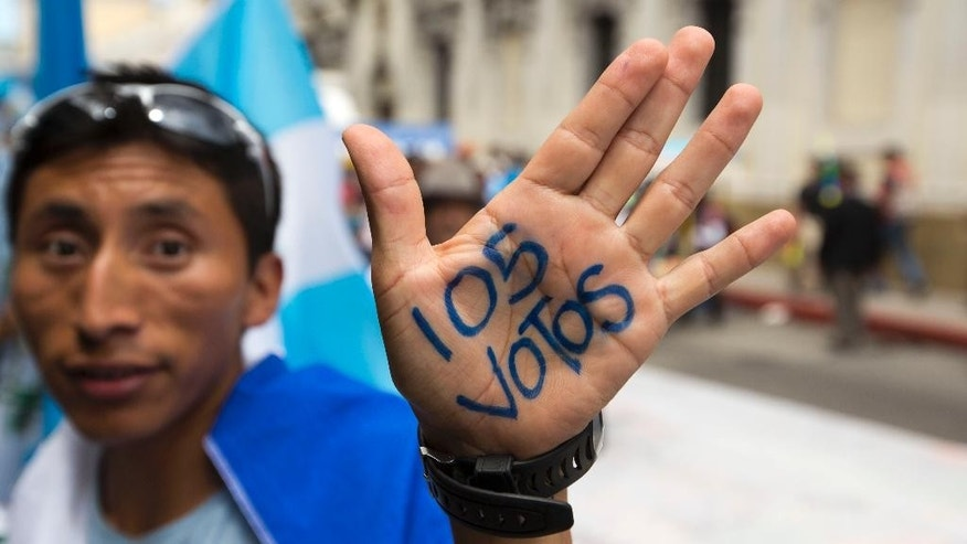 "A protestor shows off his marked hand, the ""105 votes"" in reference to the votes necessary for lawmakers to remove Guatemala's President Otto Perez Molina's immunity from prosecution, as citizens gathered outside the Congress building, in Guatemala City, Tuesday, Sept. 1, 2015. The congressional process against Perez Molina is akin to impeachment and could lead to criminal charges. (AP Photo/Moises Castillo)"