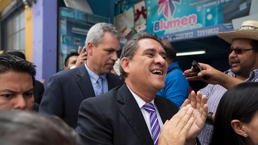 Congressman Roberto Alejos, center, arrives for a congressional session in which lawmakers will decide on whether to remove Guatemalan President Otto Perez Molina's immunity from prosecution, in Guatemala City, Tuesday, Sept. 1, 2015. The congressional process against Perez Molina is akin to impeachment and could lead to criminal charges. (AP Photo/Moises Castillo)