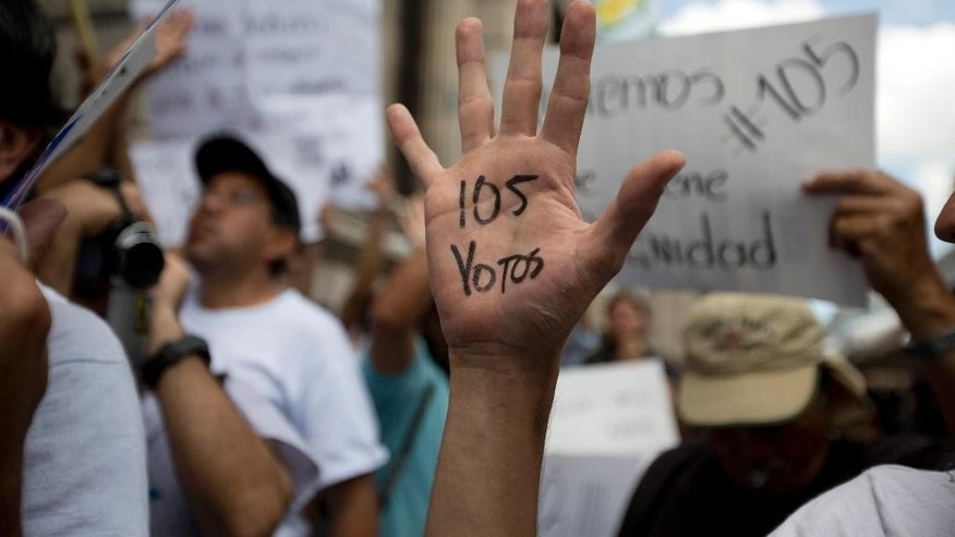 "A protestor raises his marked hand, the ""105 votes"" in reference to the votes necessary for lawmakers to remove Guatemala's President Otto Perez Molina's immunity from prosecution, as citizens gathered outside the Congress building, in Guatemala City, Tuesday, Sept. 1, 2015. The congressional process against Perez Molina is akin to impeachment and could lead to criminal charges. (AP Photo/Moises Castillo)"