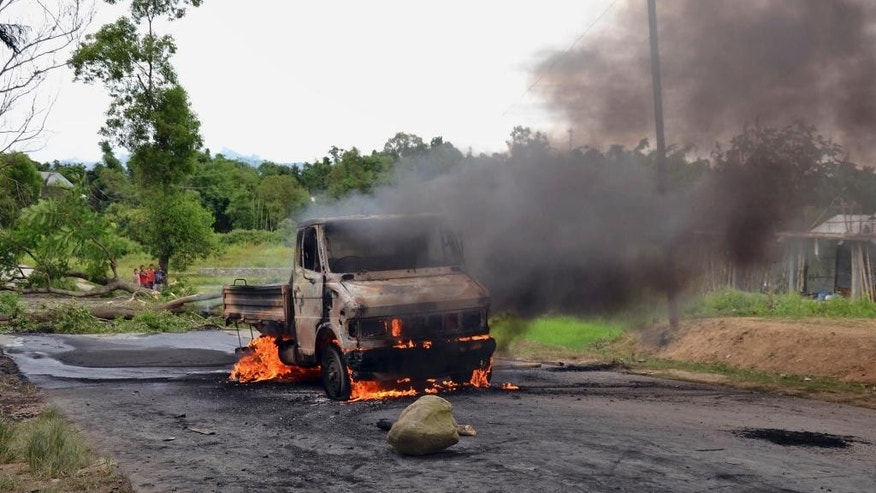 A vehicle is set on fire during a protest in Manipur, India, Tuesday, Sept. 1, 2015. Rioters set fire to the homes of seven lawmakers during a rampage to protest new legislation defining who can claim to be from the northeastern Indian state of Manipur, police said Tuesday. (AP Photo/Bullu Raj)