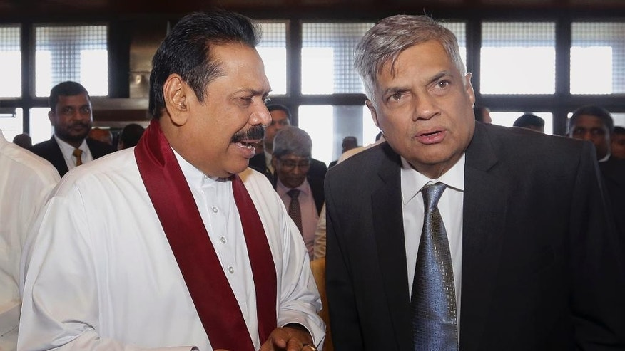 Sri Lanka's Prime Minister Ranil Wickremesinghe, right, listens to former president Mahinda Rajapaksa after the first meeting of the members of parliament since the election on Aug. 17, in Colombo, Sri Lanka, Tuesday, Sept. 1, 2015. Sri Lanka's President Maithripala Sirisena asked the country's newly elected lawmakers on Tuesday to draft political reforms to promote ethnic reconciliation and economic development in the post-war era. (AP Photo/Sanka Gayashan)