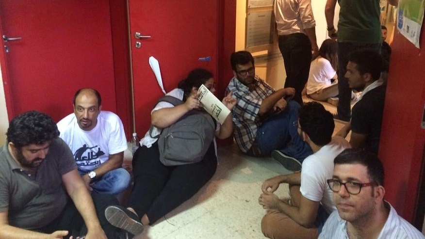 Lebanese anti-government protesters sitting cross-legged on the floor, clap and shout slogans against the minister, Mohammed Machnouk, inside the Environment Ministry, in downtown Beirut, Lebanon, Tuesday, Sept. 1, 2015. Lebanese protesters broke into the Environment Ministry in downtown Beirut Friday, demanding the resignation of the minister over the country's snowballing trash crisis. (AP Photo/Hassan Ammar)