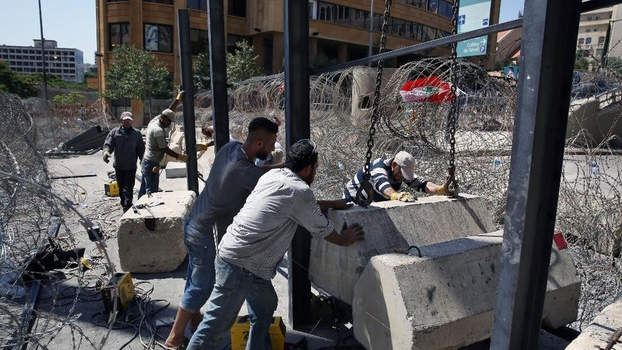 Lebanese workers install metal supports to re-enforced barricades around the perimeters of the Lebanese government building where anti-government protesters have been holding almost daily demonstrations for weeks, in downtown Beirut, Lebanon, Tuesday, Sept. 1, 2015. Lebanese protesters broke into the Environment Ministry in downtown Beirut Tuesday, demanding the resignation of the minister over the country's snowballing trash crisis. The government's failure to deal with the garbage crisis has evolved into the most serious anti-government protests in Lebanon in years with protesters seeking to challenge an entire political class that has dominated Lebanon since its civil war ended in 1990. (AP Photo/Bilal Hussein)