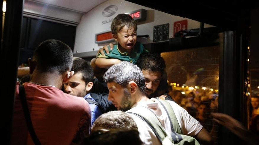 A boy cries as other migrants push to enter an overcrowded bus, transporting them to the metro station after their arrival with the catamaran Terra Jet at the Athens' port of Piraeus, on Tuesday, Sept. 1, 2015. About 1,800 refugees arrived from the northeastern Aegean island of Lesbos as the country has been overwhelmed by record numbers of migrants this year.  (AP Photo/Thanassis Stavrakis)
