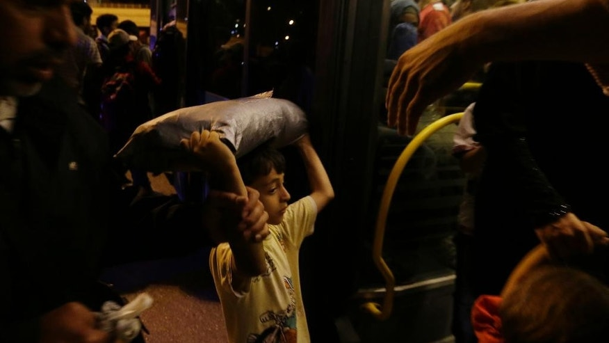 A boy with his family enters a bus transporting them to the metro station after their arrival with the catamaran Terra Jet at the Athens' port of Piraeus, on Tuesday, Sept. 1, 2015. About 1,800 refugees arrived from the northeastern Aegean island of Lesbos as the country has been overwhelmed by record numbers of migrants this year.  (AP Photo/Thanassis Stavrakis)