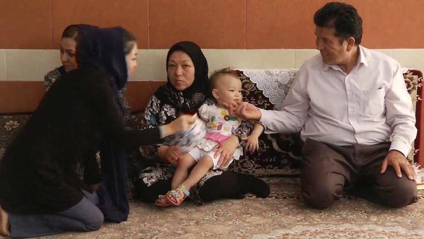In this image made from video on Monday, Aug. 31, 2015, Mohammad Bakhshi, from Afghanistan, right, and his family are seen in their home in Kashan, Iran. Bakhshi fled from Afghanistan's Badakhshan province in the 1980s, during the height of the bloody Soviet occupation. Three decades later, his son, Abdullah Bakhshi is now picking up the next leg of his family's journey to a better life, and joining the largest tide of migrants since World War II. (AP photo via AP video)