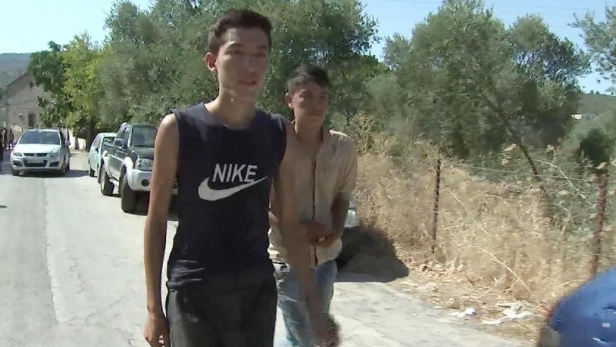 In this Aug. 27, 2015 image made from video, Abdullah Bakhshi, from Afghanistan, left, and his cousin, walk down a road along road near Moria, Greece. Bakhshi, who had been traveling for 10 days, was waiting for a spot on a ship to take him to Athens. Three decades after  his father fled war in Afghanistan to seek safety in Iran, he is now picking up the next leg of his family's journey to a better life, and joining the largest tide of migrants since World War II. (AP Photo via AP video)