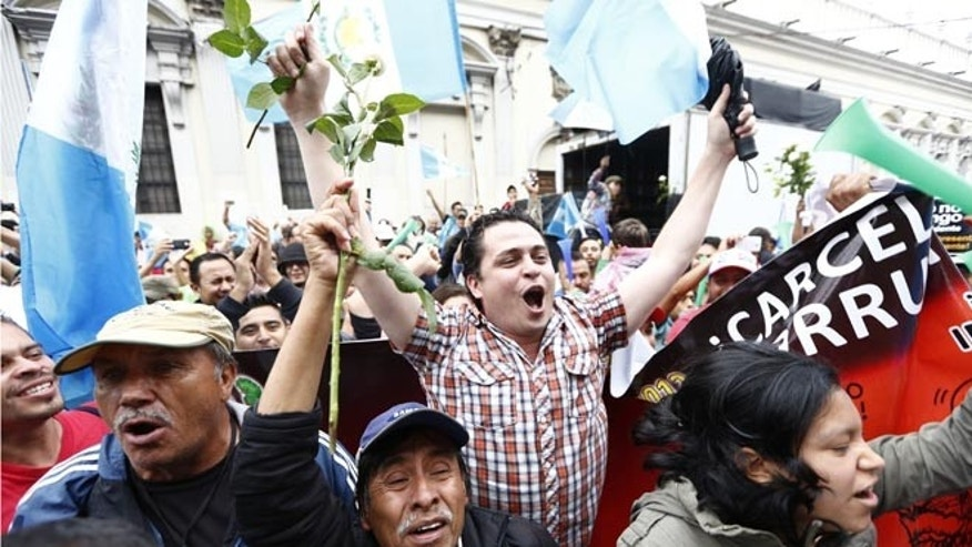 Demonstrators react in jubilation in front of the Guatemalan Congress building as they hear the news that Congress has voted to withdraw President Otto Perez Molina's immunity from prosecution, in Guatemala City, Tuesday, Sep. 1, 2015. Perez Molina's government has been beset by a series of corruption cases, but until now he has been immune to prosecution as president. (AP Photo Moises Castillo)