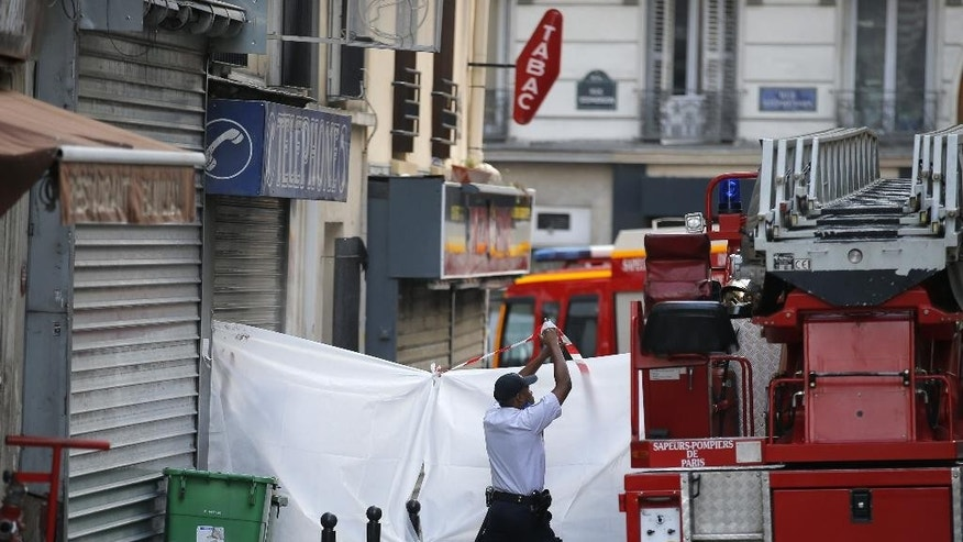 Investigators hide a building entrance after a fire broke out Wednesday, Sept. 2, 2015 in Paris, France.  Officials say eight people died in an apartment fire early Wednesday and police are investigating a possible criminal origin of the blaze. (AP Photo/Francois Mori)