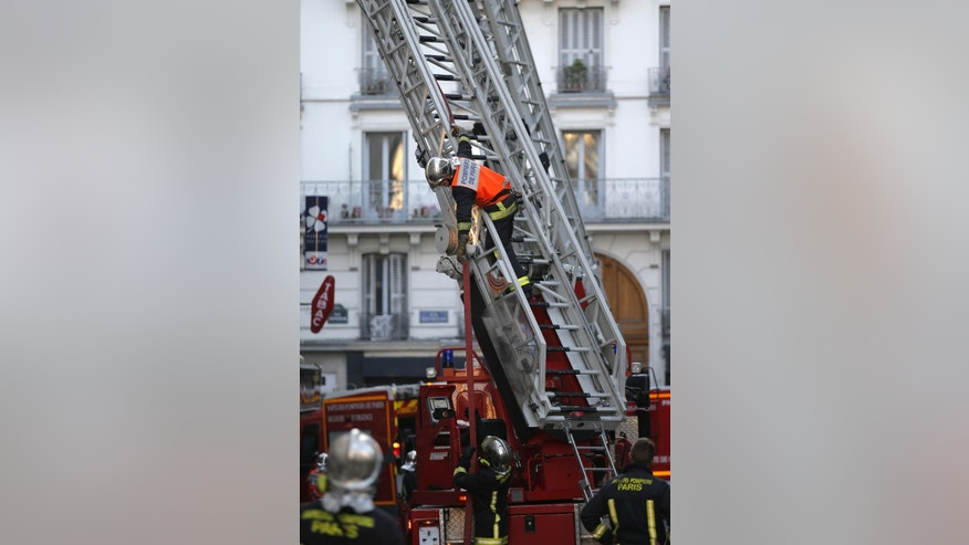 A rescue worker climbs a ladder after a fire broke out at a building, Wednesday, Sept.2, 2015 in Paris, France.  Officials say eight people died in an apartment fire early Wednesday and police are investigating a possible criminal origin of the blaze. (AP Photo/Francois Mori)