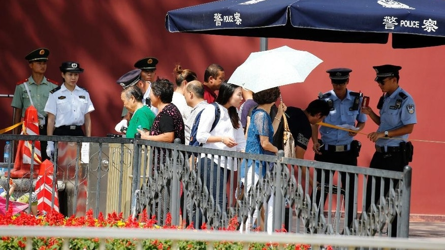 FILE - In this Aug. 27, 2015 file photo, Chinese policemen check identifications of a passerby ahead of the Sept. 3 massive military parade commemorating the end of World War II in Beijing. China will hold a massive military parade through the heart of its capital, but ordinary folks can't watch. Authorities obsessed with security and leery of any possible hitches will virtually shut down central Beijing on Thursday, Sept. 3, keeping most people out of eyeshot for the parade commemorating the defeat of Japan in World War II. Residents who live along the parade route have received notices ordering them to stay off balconies, keep windows shut, invite no guests and - at some buildings - snap no pictures. (AP Photo/Ng Han Guan, File)