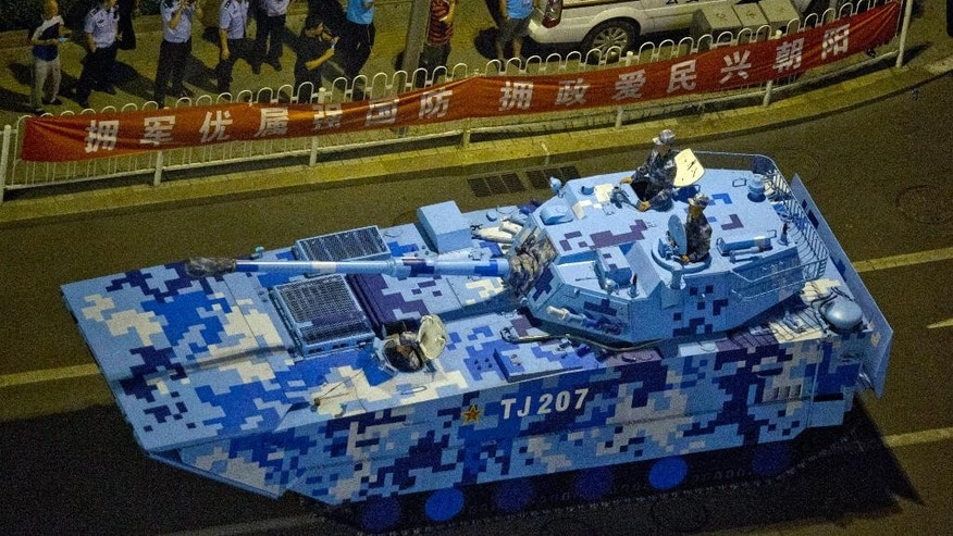 FILE - In this Aug. 22, 2015 file photo, Chinese police men stand guard as a Chinese military tank rolls down a main avenue during a rehearsal at night ahead of the Sept. 3 military parade to commemorate the end of World War II in Beijing. China will hold a massive military parade through the heart of its capital, but ordinary folks can't watch. Authorities obsessed with security and leery of any possible hitches will virtually shut down central Beijing on Thursday, Sept. 3, keeping most people out of eyeshot for the parade commemorating the defeat of Japan in World War II. Residents who live along the parade route have received notices ordering them to stay off balconies, keep windows shut, invite no guests and - at some buildings - snap no pictures. (AP Photo/Ng Han Guan, File)