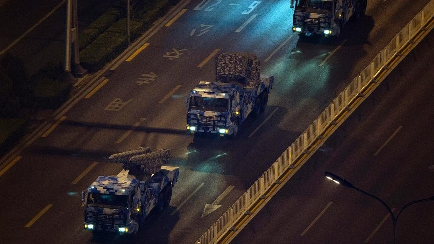FILE - In this Aug. 22, 2015 file photo, Chinese military vehicles roll down a main avenue during a rehearsal at night ahead of the Sept. 3 military parade to commemorate the end of World War II in Beijing. China will hold a massive military parade through the heart of its capital, but ordinary folks can't watch. Authorities obsessed with security and leery of any possible hitches will virtually shut down central Beijing on Thursday, Sept. 3, keeping most people out of eyeshot for the parade commemorating the defeat of Japan in World War II. Residents who live along the parade route have received notices ordering them to stay off balconies, keep windows shut, invite no guests and - at some buildings - snap no pictures. (AP Photo/Ng Han Guan, File)