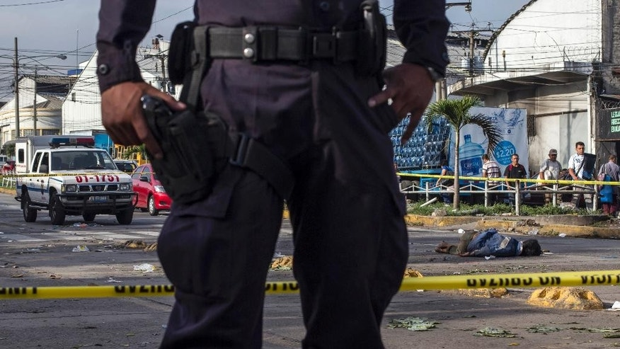 In this Monday, Aug. 31, 2015 photo, a police officer guards a crime scene after a was man killed at the entrance to a vegetable market in San Salvador, El Salvador.  Figures released by the country's coroner's office confirm the month of August as the deadliest in the country's history. (AP Photo/Salvador Melendez)