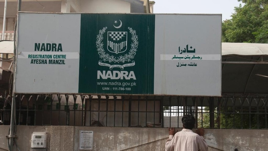 In this Tuesday, Sept. 1, 2015 photo, a man looks into the office of Pakistan's National Data and Registration Authority or NADRA which was closed by authorities in Karachi, Pakistan. Foreign Islamic militants have been able to secure Pakistani national identity cards in exchange for bribes as low as $100, giving them vastly greater freedom to operate, according to a report by Pakistan's top intelligence agency obtained by The Associated Press. The main fault in the ID scandal seems to lies with corruption in Pakistan's NADRA, the organization that issues national ID cards. (AP Photo/Shakil Adil)