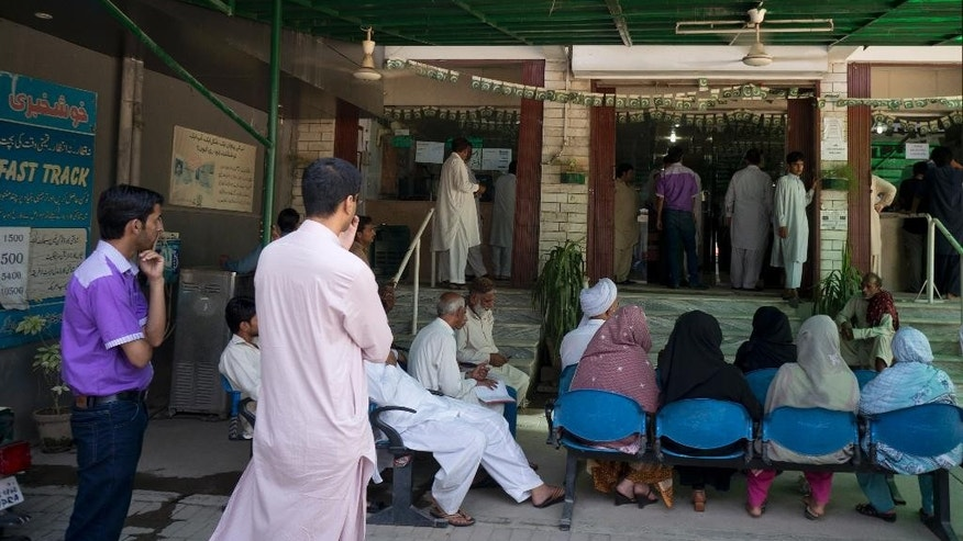 In this Monday, Aug. 24, 2015 photo, Pakistani applicants wait outside the office of Pakistan's National Data Registration Authority or NADRA to collect their identity cards in Islamabad, Pakistan. Foreign Islamic militants have been able to secure Pakistani national identity cards in exchange for bribes as low as $100, giving them vastly greater freedom to operate, according to a report by Pakistan's top intelligence agency obtained by The Associated Press. The main fault in the ID scandal seems to lies with corruption in Pakistan's NADRA, the organization that issues national ID cards. (AP Photo/B.K. Bangash)