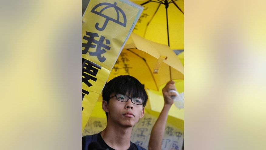 "Hong Kong teenage student leader Joshua Wong stands in front of yellow umbrellas outside a magistrates' court in Hong Kong, Wednesday, Sept. 2, 2015. Wong is set to face trial on charges relating to his role in storming government headquarters nearly a year ago in a protest that sparked monthslong pro-democracy street occupations. The banner reads ""I want genuine universal suffrage."" (AP Photo/Vincent Yu)"
