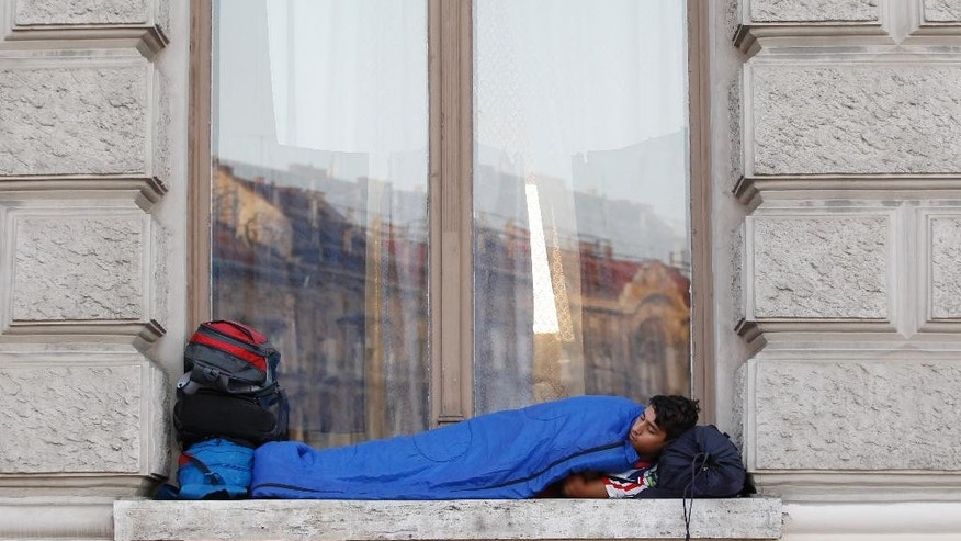 A young man sleeps in a window as migrants rest near the Keleti Railway Station in Budapest, Hungary, Wednesday, Sept. 2, 2015, after police stopped them from getting on trains to Germany. Over 150,000 migrants have reached Hungary this year, most coming through the southern border with Serbia. Many apply for asylum but quickly try to leave for richer EU countries. (AP Photo/Petr David Josek)