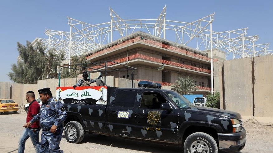 Iraqi security forces guard the entrance to a sports complex being built by a Turkish construction company, in the Shiite district of Sadr City, Baghdad, Iraq, Wednesday, Sept. 2, 2015. Masked men in military uniforms kidnapped 18 Turkish workers and engineers working at the site in Baghdad at dawn Wednesday, bundling them into several SUVs and speeding away, Iraqis security officials said. (AP Photo/Khalid Mohammed)