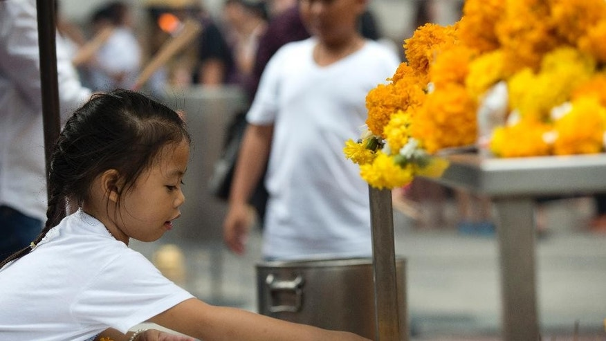 A young visitor makes an offering of flowers for Phra Phrom, the Thai interpretation of the Hindu god Brahma, at the Erawan Shrine, the scene of the Aug. 17 bombing, in Bangkok, Wednesday, Sept. 2, 2015. Thai authorities arrested a man they believe is part of a group responsible for a deadly bombing at a shrine in central Bangkok two weeks ago, the prime minister announced Tuesday. (AP Photo/Mark Baker)
