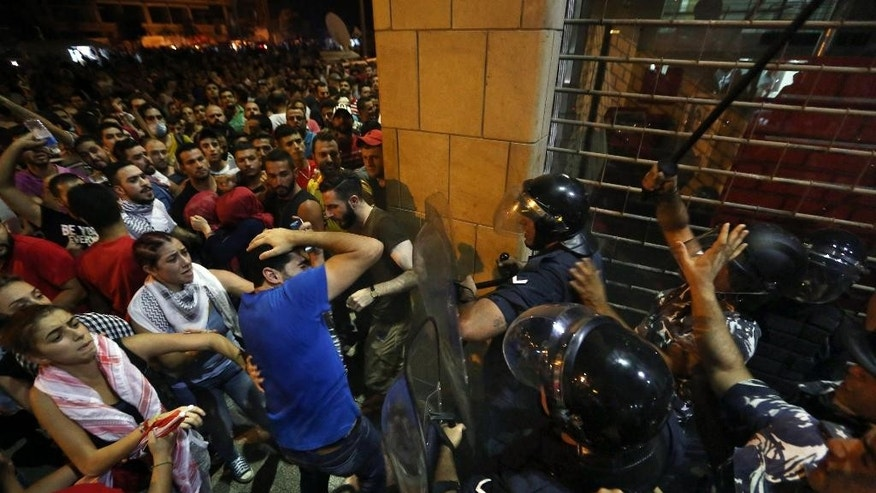 Lebanese anti-government protesters clash with riot policemen outside the Environment Ministry in support of activists staging a sit-in inside, in downtown Beirut, Lebanon, Tuesday, Sept. 1, 2015. Lebanese security forces dragged a number of activists out of the Environment Ministry in downtown Beirut, where they were staging an hours-long sit-in on Tuesday demanding the minister's resignation over a trash crisis that has ignited mass protests. (AP Photo/Bilal Hussein)