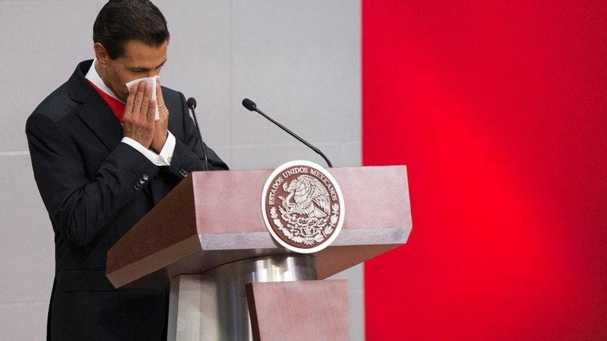 Mexico's President Enrique Pena Nieto wipes his face as he prepares to give his third State of the Nation address, inside the National Palace in Mexico City, Wednesday, Sept. 2, 2015. For the first time in recent history the government did not make the written state-of-the-nation report available publicly the day before the president's address, however the report was sent to Congress on Tuesday. (AP Photo/Rebecca Blackwell)