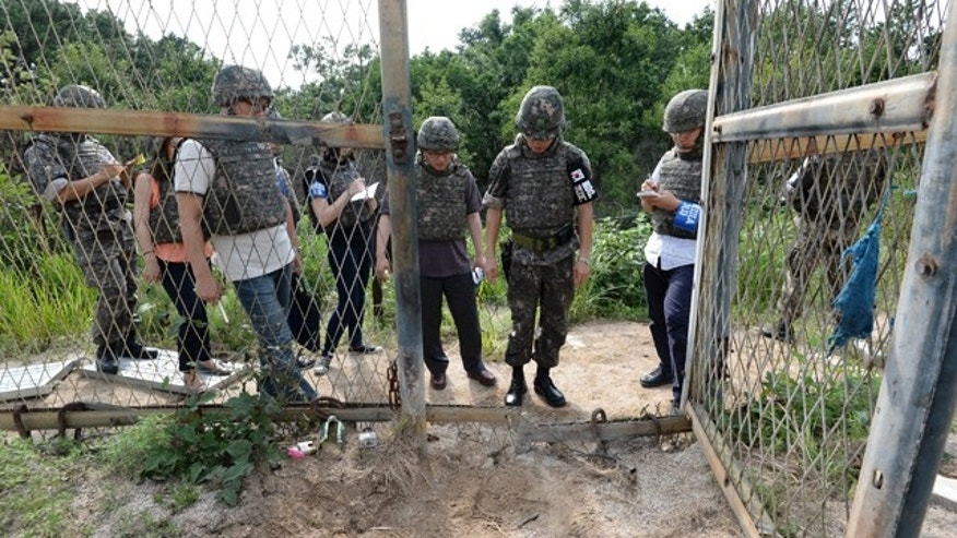 FILE - In this Aug. 9, 2015 file photo provided by the Defense Ministry, an unidentified South Korean army official, second from right, gives a briefing to the media at the scene of a blast inside the demilitarized zone in Paju, South Korea. (The Defense Ministry via AP, FIle)