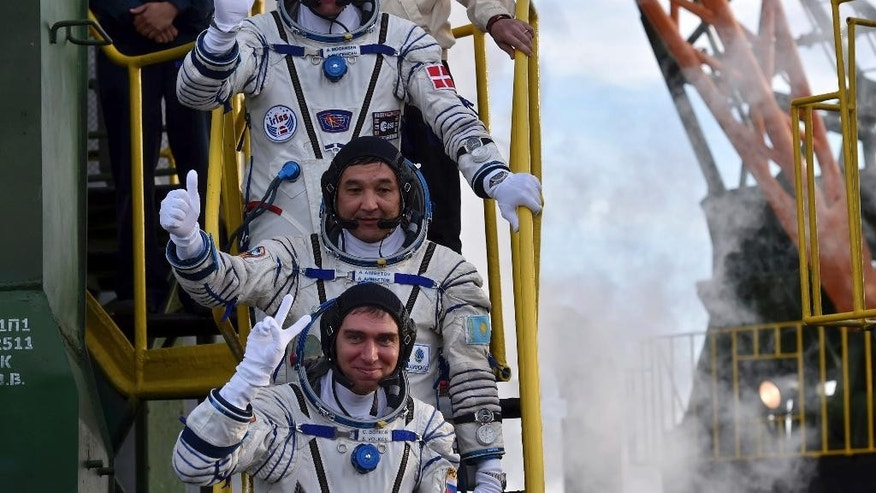 Kazakhstan's cosmonaut Aydyn Aimbetov, center, Russian cosmonaut Sergei Volkov, bottom, and Denmark's astronaut Andreas Mogensen, members of the main crew of the mission to the International Space Station (ISS), gesture near the rocket prior the launch at the Russian leased Baikonur cosmodrome, Kazakhstan, Wednesday, Sept. 2, 2015. (Kirill Kudryavtsev/Pool Photo via AP)