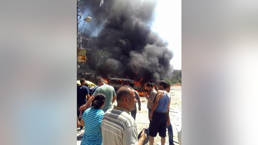 In this photo released by the Syrian official news agency SANA, Syrians gather at the site of a car bombing in the port city of Latakia, Syria, Wednesday, Sept. 2, 2015. A car bomb exploded in a square in the Syrian port city of Latakia, a stronghold of President Bashar Assad, killing at least 10 people and wounding 25, the official Syrian news agency SANA said. (SANA via AP)
