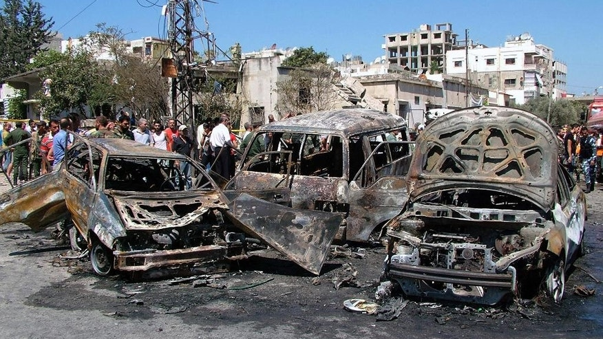 In this photo released by the Syrian official news agency SANA, residents and emergency personnel gather at the site of a car bombing in a square the port city of Latakia, Syria, Wednesday, Sept. 2, 2015. The car bomb exploded in Latakia, a stronghold of President Bashar Assad, killing at least 10 people and wounding 25, the official Syrian news agency SANA said. (SANA via AP)