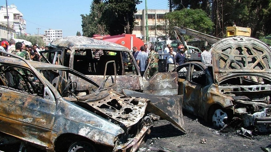 In this photo released by the Syrian official news agency SANA, residents and emergency personnel gather at the site of a car bombing at a square in the port city of Latakia, Syria, Wednesday, Sept. 2, 2015. The car bomb exploded in Latakia, a stronghold of President Bashar Assad, killing at least 10 people and wounding 25, the official Syrian news agency SANA said. (SANA via AP)