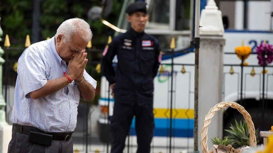 A man prays at the Erawan Shrine, the scene of the Aug. 17 bombing,  as a policeman keeps watch in Bangkok, Wednesday, Sept. 2, 2015. Thai authorities arrested a man they believe is part of a group responsible for a deadly bombing at a shrine in central Bangkok two weeks ago, the prime minister announced Tuesday. (AP Photo/Mark Baker)