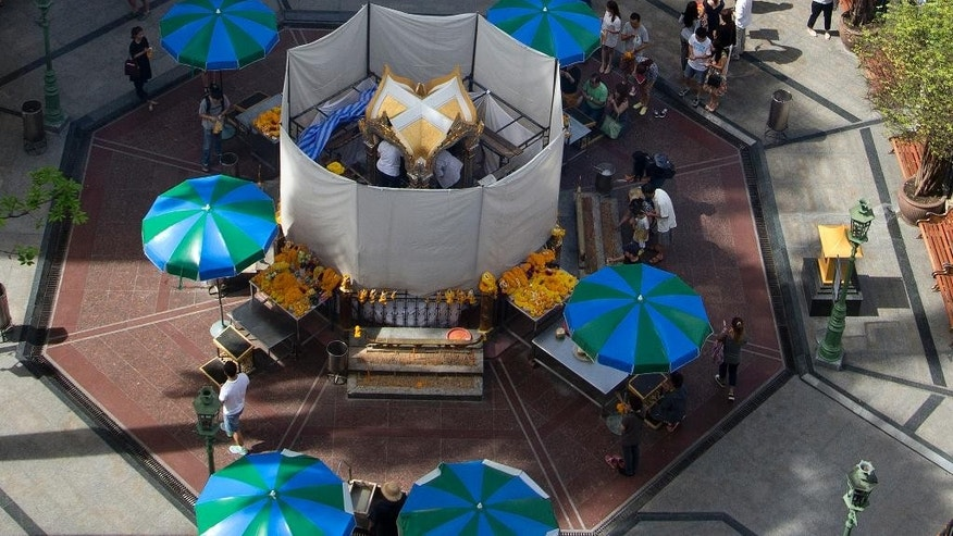 Workers repair the Erawan Shrine, the scene of the Aug. 17 bombing, as visitors line up to make offerings in Bangkok, Wednesday, Sept. 2, 2015. Thai authorities arrested a man they believe is part of a group responsible for a deadly bombing at a shrine in central Bangkok two weeks ago, the prime minister announced Tuesday. (AP Photo/Mark Baker)