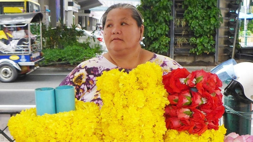 "In this Aug. 28, 2015, photo, Rudee Jiamjairat, 57, a vendor who sells flowers outside the Erawan Shrine -- the scene of a bombing two weeks ago -- is interviewed by the Associated Press in Bangkok, Thailand. ""We're not afraid. We believe the spirit of the shrine will protect us,"" said Rudee. ""When we see people carrying backpacks we tell each other to keep an eye on them. If anyone is standing around here for too long, I tell the security guard and he tells them to leave."" On the surface, the bustling city of food vendors, traffic jams and raucous nightlife is back to normal, two weeks after the Erawan Shrine bombing. But many feel a new and gnawing sense of fear and insecurity. (AP Photo/Jocelyn Gecker)"