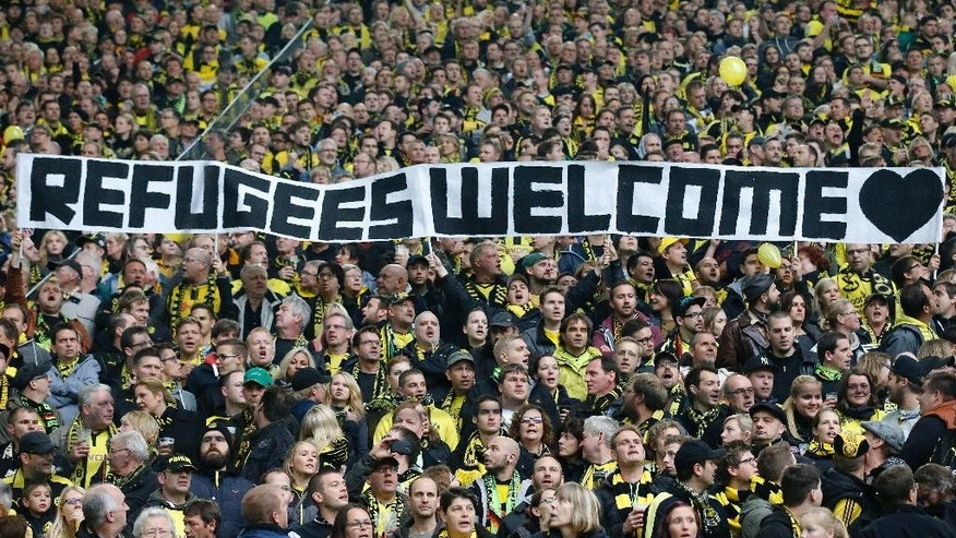 FILE - In this Oct. 25, 2014 file photo Dortmund supporters hold a banner prior the German first division Bundesliga soccer match between BvB Borussia Dortmund  and Hannover 96 in Dortmund, Germany. Traditional rivalries are being set aside for common cause as German football clubs and fans show their support across the country's stadiums for refugees fleeing war and poverty. (AP Photo/Frank Augstein, file)