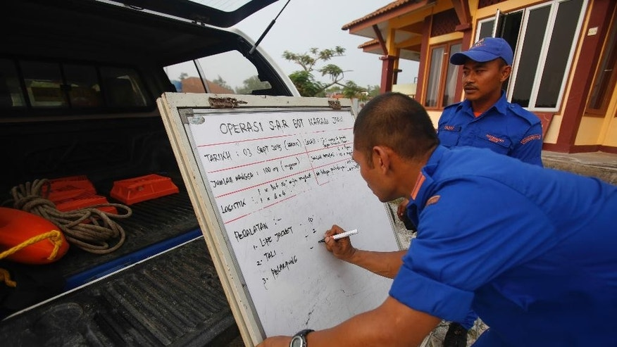 Malaysia General Defense personnel sets up a rescue chart in Sabak Bernam, Malaysia on Thursday, Sept. 3, 2015.  Malaysian officials say a wooden boat crammed with migrant workers headed back to Indonesia has capsized, leaving at least 14 people dead.(AP Photo/Joshua Paul)