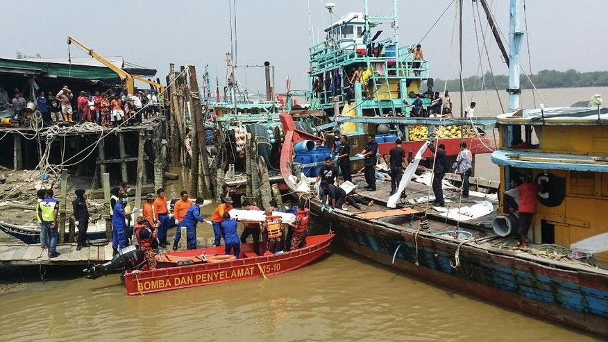 In this photo released by the Malaysian Maritime Enforcement Agency, a rescue team unload Friday, Sept. 3, 2015 a body of a victim retrieved from a search operation near the area where a boat carrying Indonesian migrants sank near Hutan Melintang, Perak state in Malaysia. Malaysian officials say a wooden boat crammed with migrant workers headed back to Indonesia has capsized, leaving at least 14 people dead. (The Malaysian Maritime Enforcement Agency via AP)