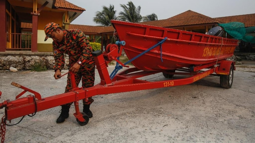 Malaysia Fire Department personnel prepare a rescue boat in Sabak Bernam, Malaysia on Thursday, Sept. 3, 2015.  Malaysian officials say a wooden boat crammed with migrant workers headed back to Indonesia has capsized, leaving at least 14 people dead. (AP Photo/Joshua Paul)