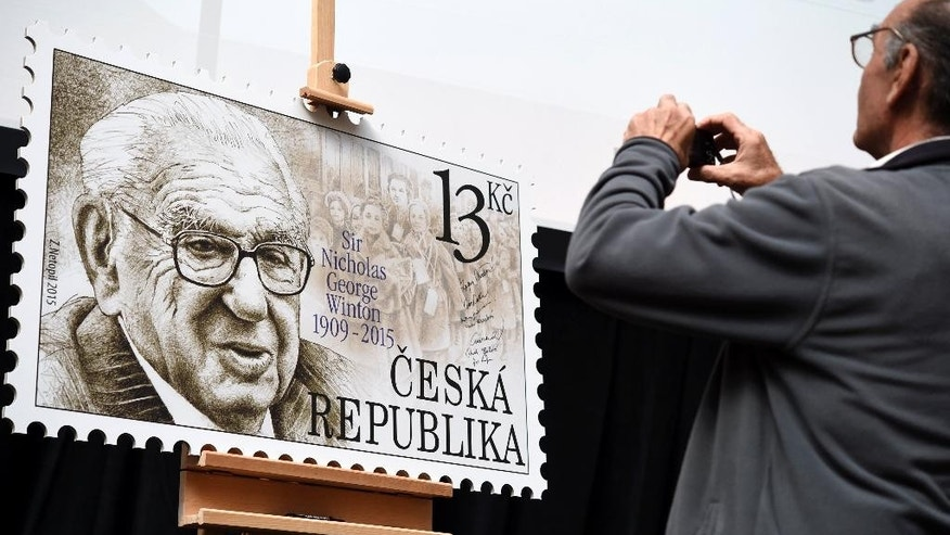 A man takes pictures of a giant postage stamp dedicated to Sir Nicholas Winton, who saved hundreds of Czech Jewish children from the Holocaust, during presentation in Prague, Czech Republic, Wednesday Sept. 2, 2015. (AP Photo, CTK/Roman Vondrous) SLOVAKIA OUT