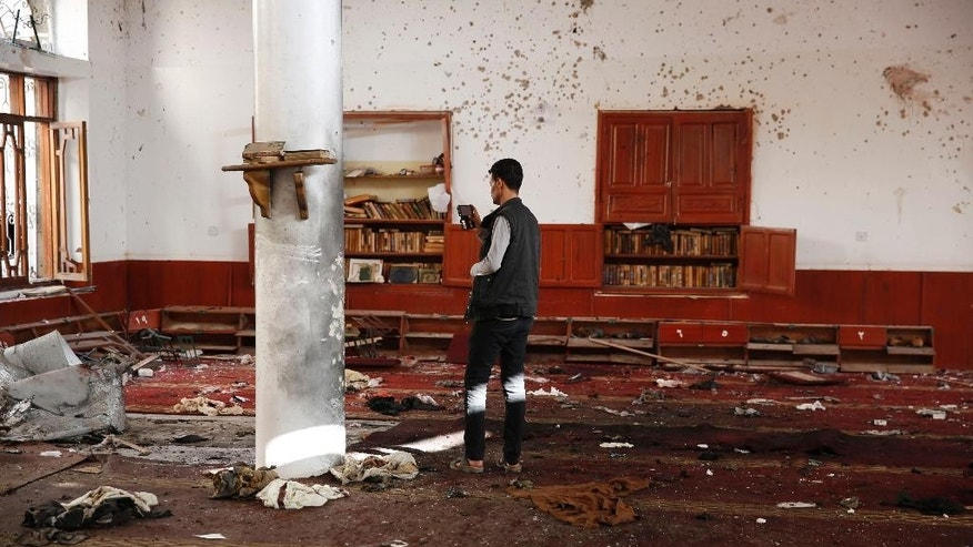 A man uses his mobile to take pictures inside a Shiite mosque hit by two bombs in Sanaa, Yemen, Thursday, Sept. 3, 2015. An Islamic State-claimed suicide bomber and a subsequent car bombing killed at least 20 people Wednesday at a mosque in Yemen's rebel-held capital, Sanaa, amid the country's raging civil war, officials said. (AP Photo/Hani Mohammed)