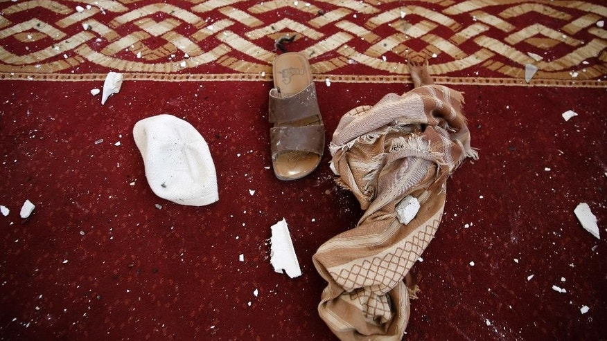 Clothes of a victim lie on the ground of a Shiite mosque hit by two bombs in Sanaa, Yemen, Thursday, Sept. 3, 2015. An Islamic State-claimed suicide bomber and a subsequent car bombing killed at least 20 people Wednesday at a mosque in Yemen's rebel-held capital, Sanaa, amid the country's raging civil war, officials said. (AP Photo/Hani Mohammed)