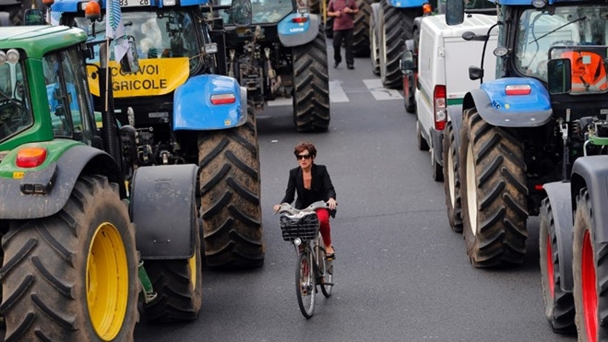 Sept. 3: : A woman rides her bike between tractors as angry farmers demonstrate in Paris.
