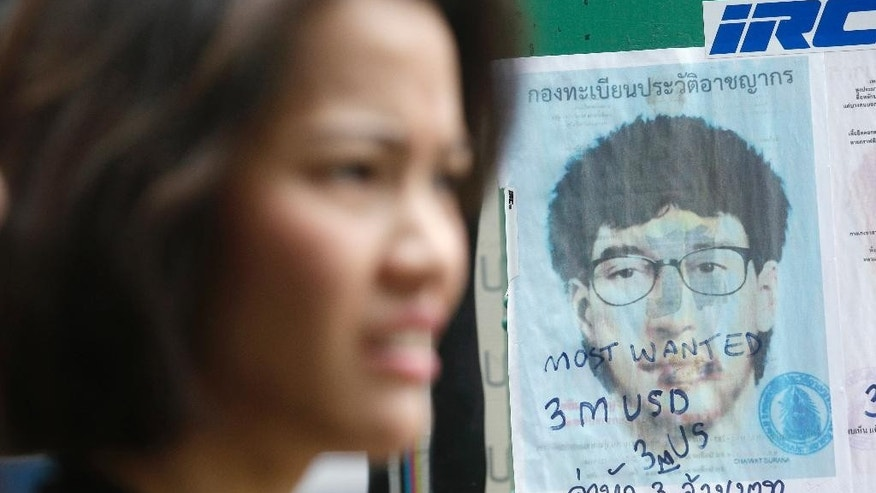 In this Aug. 28, 2015, photo, a woman walks past a poster of a sketch of what the Thai officials have called the main suspect they are seeking for the Aug. 17 Erawan Shrine bombing in Bangkok, Thailand. Bangkok's laid-back vibe has toughened a bit in the aftermath of last month's deadly bombing in the heart of the city. Security appears tighter, with a more conspicuous contingent of police, soldiers and plainclothes officers patrolling and guarding tourist areas and public places that attract crowds. (AP Photo/Sakchai Lalit)