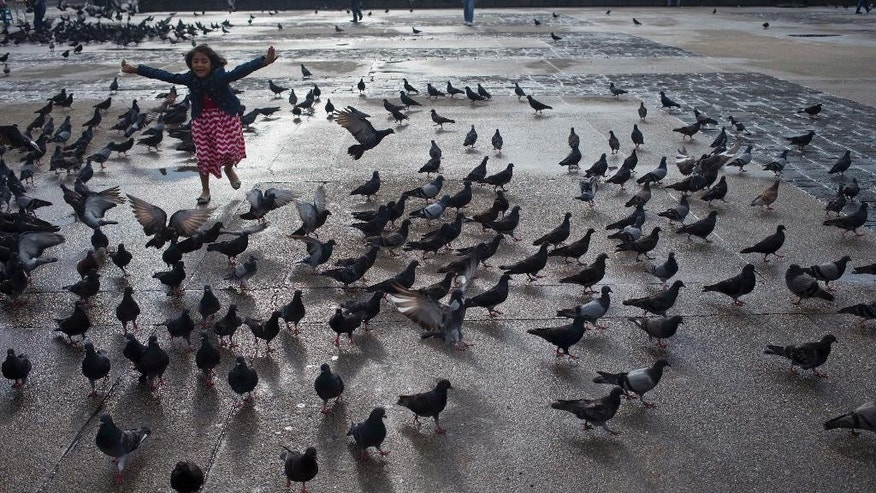 A girls plays with pigeons in Constitution Square in Guatemala City, Wednesday, Sept. 2, 2015. (AP Photo/Esteban Felix)