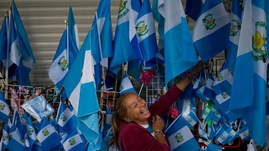 A street vendor of Guatemalan flags smiles around the Constitution Square in Guatemala City, Wednesday, Sept. 2, 2015. As Guatemala's presidential campaign builds to a climax, the biggest rallies of all have been demands to call off the election itself scheduled for Sept. 6. Tens of thousands have taken to the streets in protest amid a roiling series of corruption scandals that have a former vice president behind bars accused of taking millions in bribes, and President Otto Perez Molina stripped of his immunity from prosecution and facing possible criminal charges and removal from office.  (AP Photo/Esteban Felix)