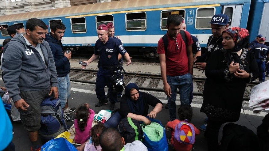 Hungarian policeman tries to organize people as hundreds of migrants try to board a train at the Keleti Railway Station in Budapest, Hungary, Thursday, Sept. 3, 2015. Over 150,000 migrants have reached Hungary this year, most coming through the southern border with Serbia. Many apply for asylum but quickly try to leave for richer EU countries. (AP Photo/Petr David Josek)