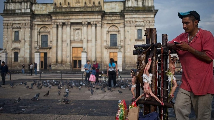 A stret vendor of religious images checks his mobile phone, at Constitution Square in Guatemala City, Wednesday, Sept. 2, 2015. (AP Photo/Esteban Felix)