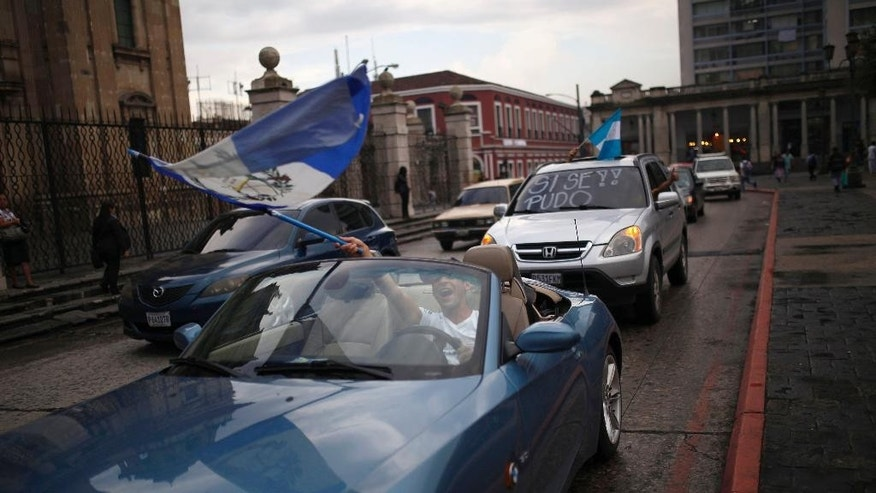A driver waves a Guatemala flag as he celebrates that Congress voted to withdraw President Otto Perez Molina's immunity from prosecution, in Guatemala City, Tuesday, Sep. 1, 2015. Perez Molina's government has been beset by a series of corruption cases, but until now he has been immune to prosecution as president. (AP Photo/Luis Soto)