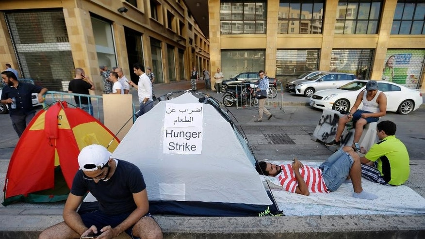 Lebanese activists hold a hunger strike outside the Environment Ministry in downtown Beirut, Lebanon, Thursday, Sept. 3, 2015. Several Lebanese activists launched an open-ended hunger strike on Thursday, demanding the resignation of the environment minister at the center of the country's trash crisis. The activists set up tents outside the Environment Ministry in downtown Beirut. Several supporters joined the 11 hunger strikers Thursday evening. (AP Photo/Hassan Ammar)